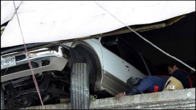 Aseguran vehículo que estuvo a punto de caer de estacionamiento