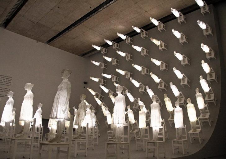 Figuras iluminadas de personas que abarcan una gran pared oscura