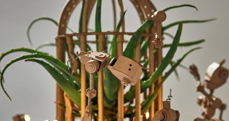 Una escultura de cartón de robots conteniendo una planta de aloe