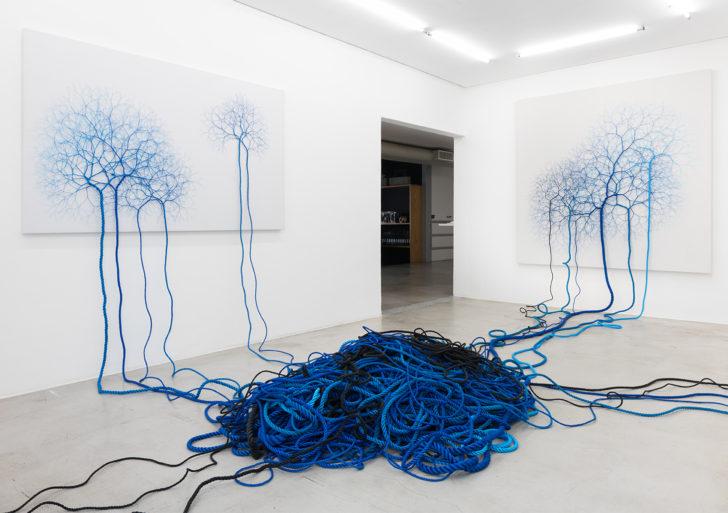 Cuerdas desenvueltas salen de lienzos y cubren el piso y el techo