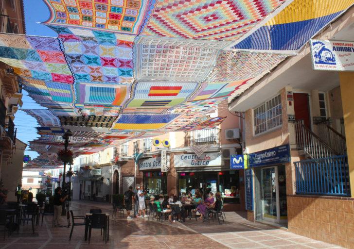 Un techo de textiles de colores cubren esta calle del sol